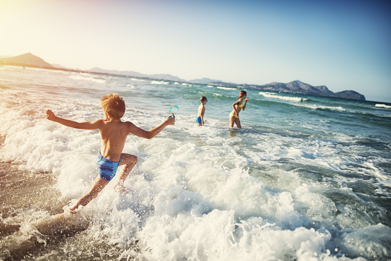Three kids - a girl and two boys - are having fun in sea. Little boy is running and jumping in the sea, his brother and sister already standing in the sea.
