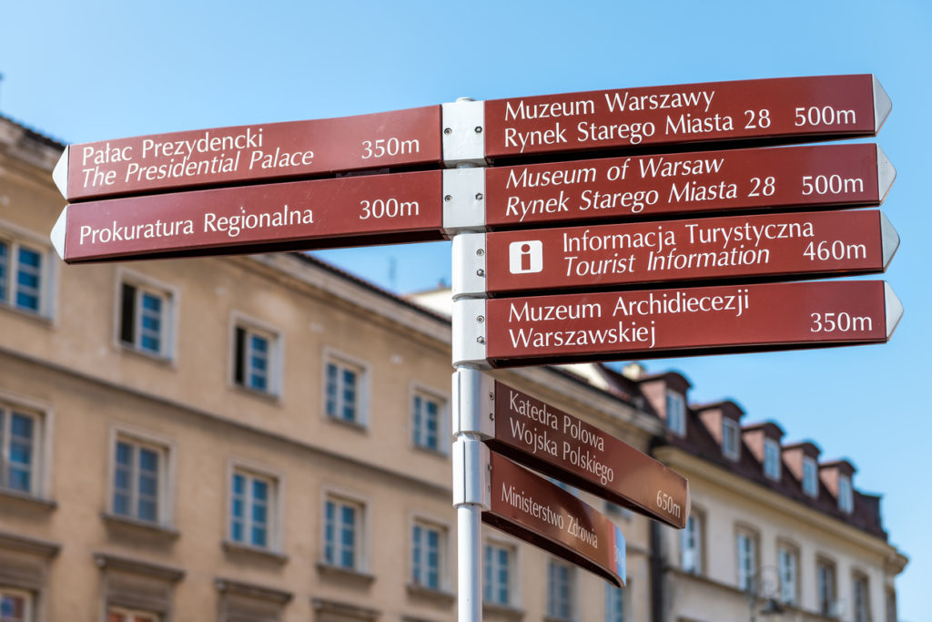 Warsaw, Poland Old town historic street city during sunny summer day Krakowskie Przedmiescie and direction information sign